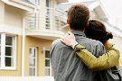 Paar umarmt sich vor einem Haus