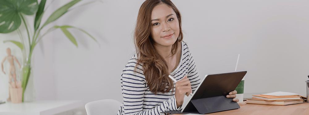 Studentin mit Tablet am Schreibtisch